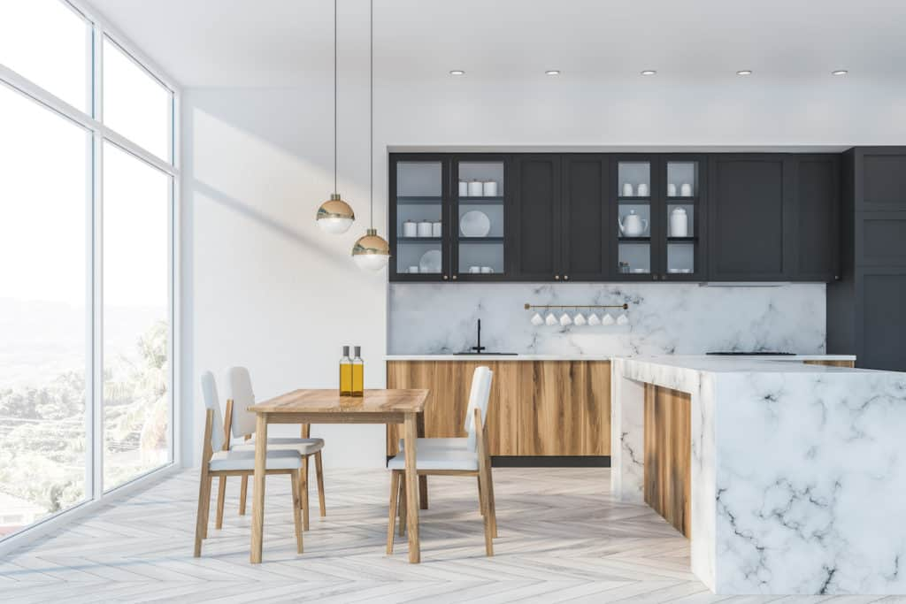 Interior of luxury kitchen with white and marble walls, wooden floor, large window, wooden countertops, gray cupboards, marble island and dining table with white chairs. 3d rendering